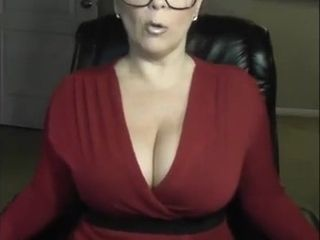 Cute looking sexy cougar in glasses is prepared to show her uber-sexy funbags